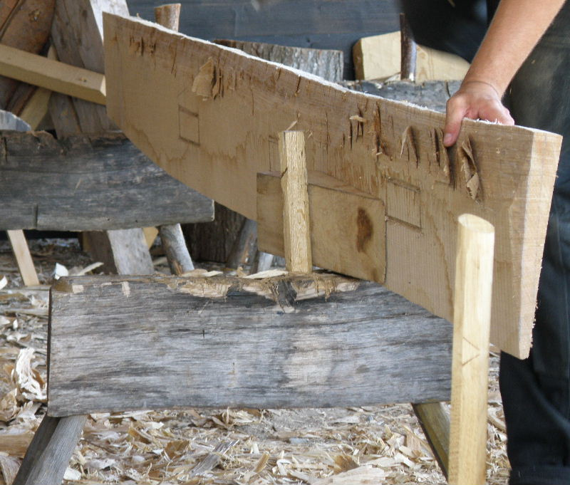 Mike the boat-builder is thinning this plank to make a strake. He has worked his way along the plank, axing into the wood to lift, but not remove, chips from the surface.