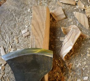 Gently curving marks on the wood surface show where the axe stopped each time, to remove the chips that are left scattered on the chopping-block.