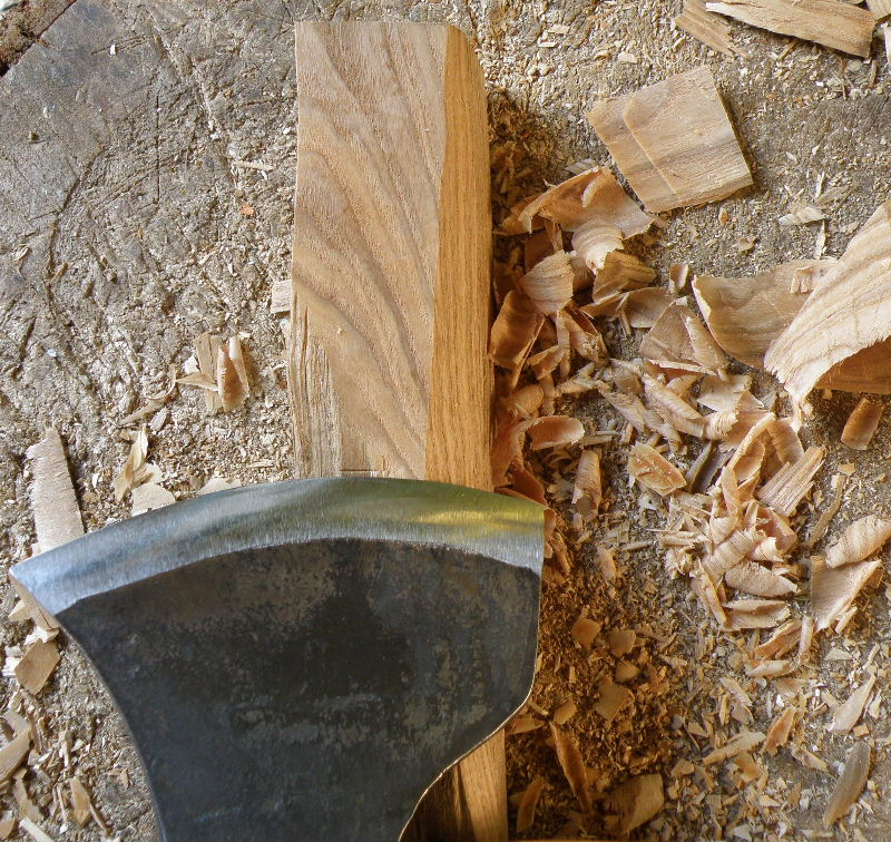 Using the same axe to shave away slivers from the wood removes the evidence of the previous cuts. The small, thin shavings lie scattered on the chopping-block.
